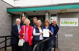 Fakenham Community Archive committee members Alan Leventhall, Howard Young, Anna Coburn, Mo Bruce, Lyn Maple, Chris Chalk and Peter Boggis, show off their CAHG Sustained Achievement award certificate outside Fakenham library.