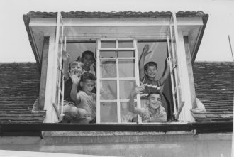 A group of boys wave from one of the windows in their accommodation in the Stables complex. Left from top: Arnold, Richard and Juek. Behind the centre glass: Stachek.  Right from top: Leonard and Niko. | From the earlypestalozzichildren.org.uk website