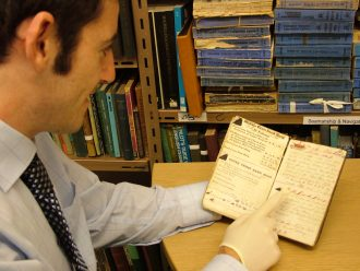Joe Carr, Curator of Great Yarmouth Museums examining a hand written notebook of Horatio Carter of Great Yarmouth from 1865.