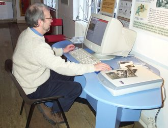 Volunteer Gerry Allen entering loaned items onto the data base