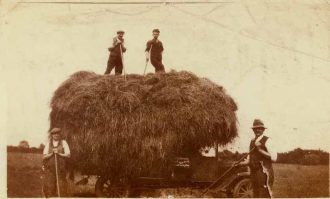 The first mechanised harvest in 1934. Those pictured are: Charles P. Headland and Lance Vale on the stack, and Charlie Headland and Harry Johnson ('Builder Johnson') on the ground.