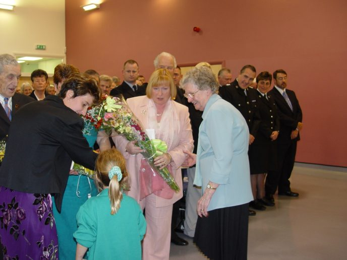Amy-Leigh Daniel of Ogmore Vale Primary School, presents a bouquet to Edwina Hart AM, MBE. Joanna Daniel and Peggy Hughes look on.
