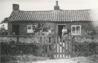 John and Eizabeth Walker, outside their cottage on Main Street, Upper Poppleton, c. 1896