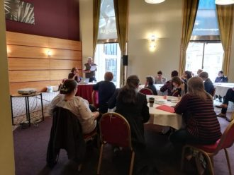 The conference included several breakout sessions, including this one about migration stories in the LGBT+ community, with Ourstory Scotland. A number of people are sat round a table